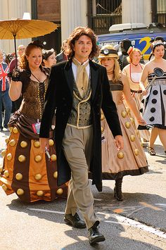 Cosplay of the 8th Doctor followed by girls in Dalek dresses. Whovians rule.