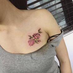 Tatuaje de dos rosas de color rosa en el pecho. Artista...