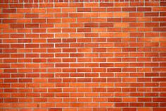 A brick wall is ordered as it is stacked up in a set pattern. (Order)