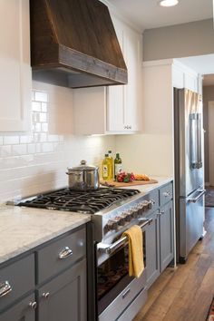 The vent hood in the Ivy's renovated kitchen has been covered with dark wood that corresponds with the support beams of the open-concept living area, as seen on HGTV's Fixer Upper.