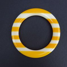 Vintage 80s 2 Striped Thin Bangle Yellow/White. Yellow and white stripped thin plastic bangle. Stripes are molded, not painted. Length: 11 inches Width: 3 1/2 inches Materials: Plastic Condition: Very