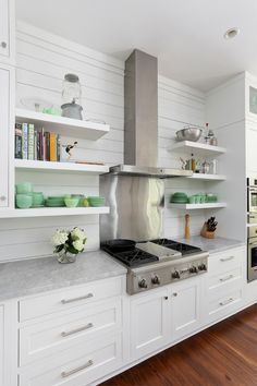 white cabinets, mid-tone hardwood floors, nickel hardware, floating shelves, planked wall