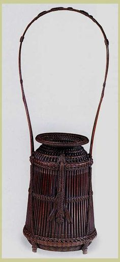cylindrical basket (left), 1921,  with vertical slats and a loop handle is accented by a row of insect stitches  ending in knots that resemble cicadas; signed by its maker, Chikuunsai I  (from Flying Cranes Antiques Ltd.).