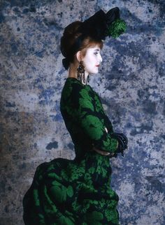 A model wears a Christian Lacroix dress from his 1987 spring-summer haute couture line for Patou. The 19th century-style dress is emerald green and black, with a bustle.