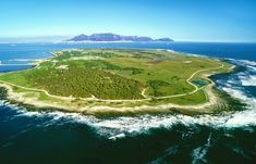 """Robben Island is an island in Table Bay km west of the coast of Bloubergstrand Cape Town, South Africa. The name is Dutch for """"seal island."""" Robben Island is roughly oval in shape km long north-south and km wide with an area of km. Prison, Best Tourist Destinations, Tourist Places, Ocean Habitat, World Of Wanderlust, Table Mountain, Fauna, World Heritage Sites, Cape Town"""