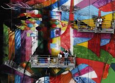Brazilian graffiti artist Eduardo Kobra (center) puts the final touches to his 56-meter tall artwork in tribute to architect Oscar Niemeyer, one of the 20th century's most influential modernist architects, at the financial center on Sao Paulo's Avenida Paulista, January 22, 2013. (Reuters)