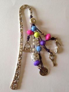 Marcapaginas con motivos de decoración variados como un zapato de tacón, moneda, llave, bolso y diferentes cuentas e colores y metálicas