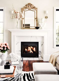 Marble fireplace with gold mirror resting on top.