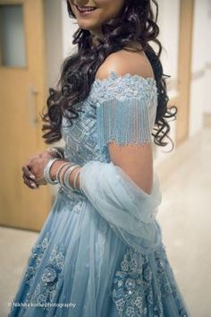 Looking for Light blue engagement lehenga with tassels on sleeve? Browse of latest bridal photos, lehenga & jewelry designs, decor ideas, etc. on WedMeGood Gallery. Indian Wedding Gowns, Indian Gowns Dresses, Indian Bridal Outfits, Indian Designer Outfits, Designer Dresses, Wedding Dress, Prom Dresses, Lehnga Dress, Saree Blouse