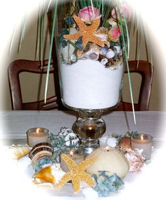 Close up of sand, seashells & candles