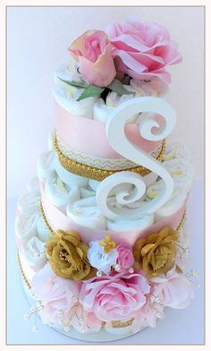 This Beautiful combination of flowers and diapers is a wonderful choice for your baby shower. Pink ribbon and Gold accents surrounded by blooming flowers makes it perfect for any season. Turn your baby shower tables into beautiful displays using our Beautiful Floral Diaper Cake.