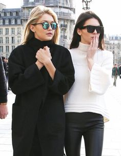 Kendall Jenner wears a white ribbed sweater, leather trousers, and rectangular sunglasses, Gigi Hadid wears a black coat and mirrored sunglasses