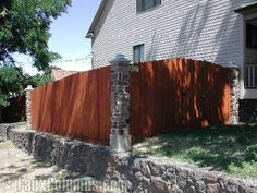 Faux stone columns in Ashford River Rock anchor a wooden privacy fence, blending in perfecting with the stone retaining wall.