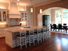 Dream kitchen complete. White Ice granite, Carrera white 3x3 Baroque Mosaic for backsplash, brick wall accent, winter gold orb fixture; and IKEA barstools!