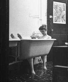 Jo Ann Kemmerling reading a book while taking bath, 1954