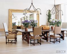 The dining area in this New York loft features a mirror frame that was salvaged from a chateau, chandeliers from Holly Hunt, and 18-century from Lucca & Co. The grand presence of this mirror, which has the effect of a large-scale work of art, help to unite the other elements of the space, creating an inviting area for meals.