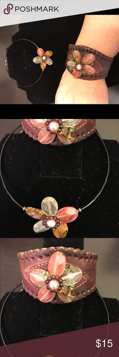 Flower choker and leather bracelet set This cells as a set. The choker is an expandable choker with a bead flower accent piece in the front. The bracelet is leather with a matching flower accent. Jewelry Necklaces
