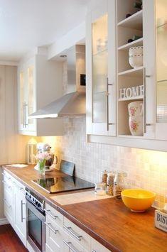 Simple kitchen - white cabinets, glass tile backsplash, wood countertops