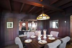 Adjacent to the living room, the dining room also has wood paneling and a beamed ceiling. Photo: Courtesy Of Obeo Arts And Crafts House, Home Crafts, Craftsman Dining Room, Angled Ceilings, Glass Front Cabinets, Built In Seating, Living Spaces, Living Room, Brick Fireplace