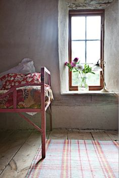 love the colored bed linen in this very white rustic room - wooden frame works well