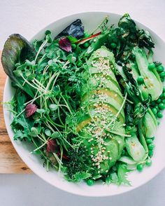 EAT YOUR GREENS Not just on St, Patrick's Day! You sure won't with this green #salad bowl with wild herbs, lettuce, radish sprouts, grilled pak choy, green peas and the most perfect avocado (@thehungrywarrior)