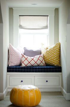 By squeezing a bench into an unused dormer you get bonus seating without taking up precious space. Here, a navy cushion and patterned pillows makes this space cozy — and stocky drawers help you stay organized. See more at Design Sponge »   - HouseBeautiful.com