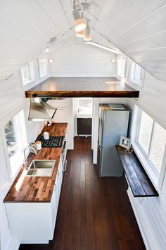 The galley style kitchen features a freestanding range and 10.1 cubic foot refrigerator. Also included is a bar style folding table, pullout trash can, and pantry.