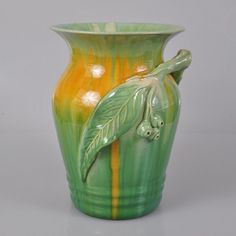 Remued Pottery large flared vase with an applied gum leaf, three gumnuts and a branch handle. Green and yellow drip glaze. From the early Remued series, dating between 1934-1940