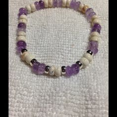 Amethyst White Turquoise Bracelet Crafted from small genuine purple amethyst and white turquoise beads, this dainty stretch bracelet will add a classy touch to any outfit! .925 sterling silver spacers give it a shiny accent. It's on elastic cord, so one size fits all. PeaceFrog Jewelry Bracelets