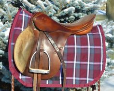 """Lovely Plum and Grey saddle pad that we determined looks stellar on black horses! This lovely saddle pad is professionally made with the highest quality products we could find. Rugged Tartan with a 400g fill and lined with a breathable wool that is great at wicking excess moisture off your horse and remains breathable and comfortable. 23"""" spine, shown with an 18"""" cross country saddle.   Machine wash cold, line dry and enjoy!"""