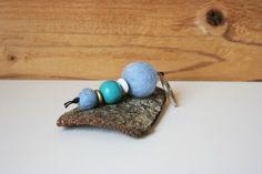 Schlüsselanhänger mit Filzkugeln in unterschiedlichen Größen in hellblau, selbstbemalte und matt lackierte Perle in helltürkis (bemalt mit Acrylfarbe), Holzlinsen in weiß und goldfarben. Aufgefädelt auf eine schwarze Kordel. Dieser Schlüsselanhänger hat eine Länge von ca. 10,5 cm.