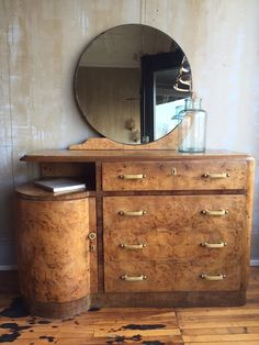 This Italian art deco dresser and mirror set is wonderful. The wood is a burl maple. The handles and keyhole locks are made out of Bakelite which was the material also used for stylish bracelets and o