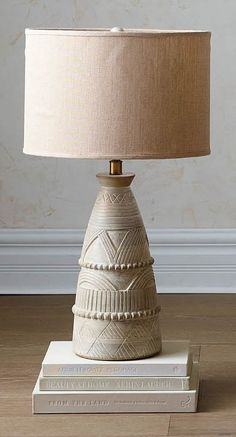 Intricately carved architectural patterns and natural variations in the wood give each refined, handcarved solid wood lamp a rustic allure. A linen shade and matching finial help complete the look.