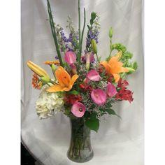 Vase arrangement of hydrangea, lilies,larkspur, callas, orchids.  Bright colors of spring.