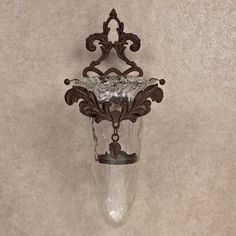 """The GG Collection, Goods for the Home  Accessories Collection  Glass Wall Sconce with Metal Hanger  GG 91131    The GG Collection, Glass Wall Sconce with Metal Hanger, 91131 is ideal for entertaining or everyday use. Fill it full of fresh flowers or a candle. Treat yourself and your family to beauty and function with The GG Collection. Care: Hand wash with mild soap and dry with a soft cloth. Dimensions: 22.5"""" H x 10"""" W  $250.00  www.lovelygifts.com"""