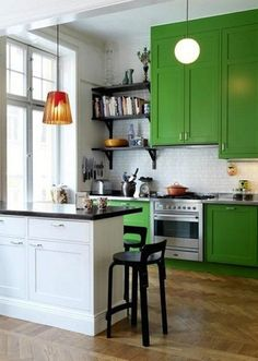mix of Kelly green and white cabinetry with open shelving and subway tile plus dark wood flooring