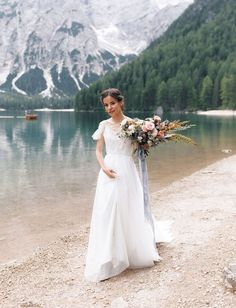 Italian Dolomites Elopement. Canoe Boats in Lago di Braies. Places to Elope. Mountain Elopement Ideas. Bohemian Wedding Dress with Butterfly Sleeves