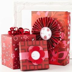 Playful gift toppers up the fun factor of these graphic red-and-pink packages! http://www.bhg.com/christmas/gift-wrapping/pretty-gift-wraps-and-bows/?socsrc=bhgpin121814flowerpowergiftwrap&page=4