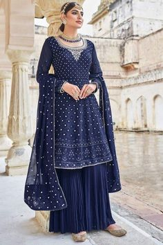 Immerse yourself in the world of elegant and traditional world by wearing this indigo blue georgette sharara suit which exudes feminine charm. This u neck and full sleeve suit prettified with resham, thread and silver zari work. Paired with georgette sharara pants in indigo blue color with indigo blue georgette dupatta. Sharara pants is plain. Dupatta beautified with resham, thread and silver zari work. #shararasuits #malaysia #Indianwear #weddingwear #andaazfashion Indian Attire, Indian Wear, Garara Suit, Wedding Mint Green, Pantalon Cigarette, Bollywood Dress, Sharara, Salwar Kameez, Georgette Fabric