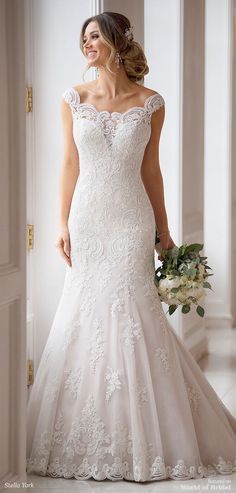 Sheer, lace off-the-shoulder sleeves give this romantic, princess-style wedding dress a unique, boho feeling. Wedding dress designer Stella York has created a stunning silhouette in lace and tulle that pops with shimmering beadwork. Placed lace is designed in a V-pattern across the waist, drawing it inward to slim the bride's figure.