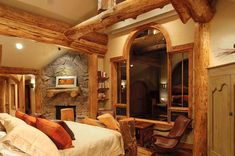 The large arched windows permit lots of natural light in and are flanked by interesting character logs in the bedroom of this log accent or hybrid log house.  Here is another example of a log mantle over a stone fireplace. The character Lodgepole pine logs allow for a rustic cozy atmosphere.  http://www.sitkaloghomes.com/