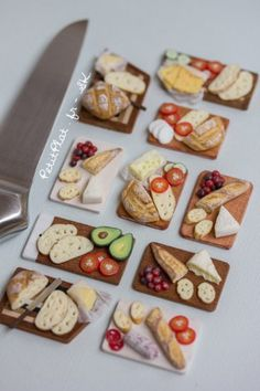 Miniature sandwiches preparation boards. Various miniature breads and baguettes that are being filled with different ingredients : cheese, mozzarella, camembert, grapes, tomatoes, salami, cucumber, butter and avocado.