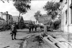 Des GI's du 318th Inf. de la 80th US ID remontent le boulevard Victor Hugo à Argentan, le 20 août 1944. On distingue de servants de mitrailleuses et un medic.  Le bâtiment sur la droite est l'école maternelle Victor Hugo, un cadavre allemand est visible devant l'entrée.  Une autre photo prise sous cet angle avec une jeep et un soldat de la 2ème DB