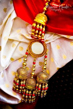 Bridal Details - Gold and Mirror Latkan with Hanging Beads | WedMeGood  #wedmegood #indianbride #indianwedding #bridaldetails #latkans #red #white #gold