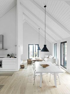 Ship lap slanted ceilings with exposed beams painted white, low-hanging black conical pendant lights, blonde wood flooring, built-in media console in the sunken living room, solid wood dining table and metal-legged contemporary dining chairs in the dining area, all rendered in a modern monochromatic palette of black and white.