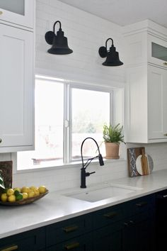 Love these black sconces❤️💡They have a transitional feel mixed with a little farm house flair. They contrast that white subway tile and quartz countertop so beautifully, while matching the faucet and wood cutting boards. #kitchenremodel #kitchendesign #subwaytile #greencabinets #transitionalkitchen #farmhousekitchen #farmhousestyle #whitecabinets #shakercabinets #whiteshakercabinets #kitchenfarmhouse #kitchenideas #kitchenlighting #kitchenlightingfixtures #kitchenlightingoversink…