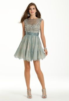 Long Paige beaded illusion bodice with two tone lace skirt and satin cummerbund.<br><br>•Illusion neckline<br>•Keyhole back with single top closure<br>•Lace bodice<br>•Pleated skirt with uneven hem