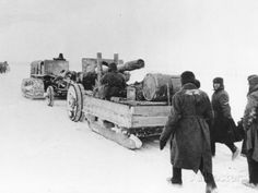 A Soviet army tractor pulls a sled with equipment and a large gun, as members of the artillery crew walk behind, underway to the forward fro...