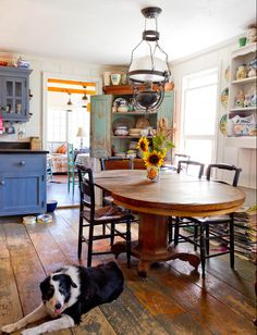 kitchen/dining area. Antiques, distressed paint, beautiful dog on floor.