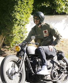 Bend it like Beckham! David cut a trendy figure in a patriotic England rose bomber jacket as he raced around on motorbike in Beverly Hills, Los Angeles on Friday afternoon